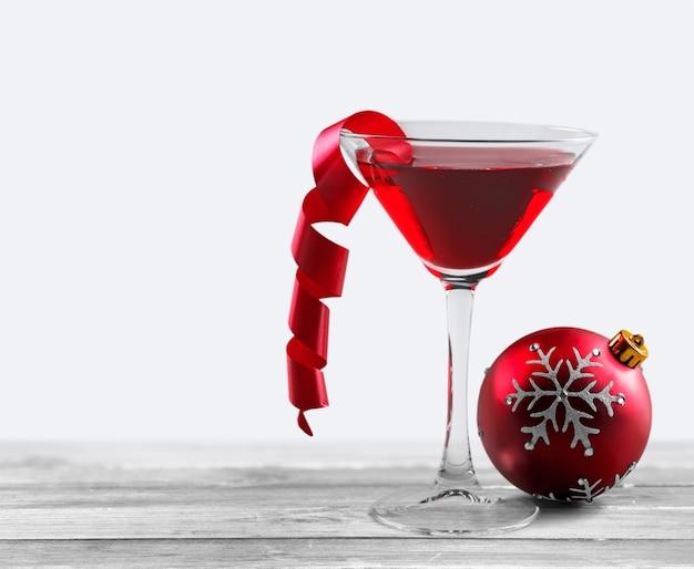 Glas rode wijn en kerstversiering op achtergrond