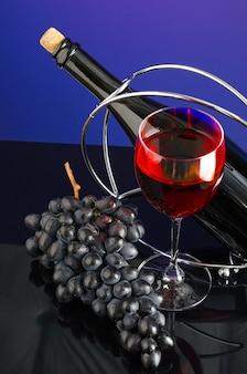 Glas rode wijn, fles en borstel de blauwe druiven op de felgekleurde achtergrond.