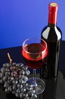 Glas rode wijn, fles wijn en borstel van blauwe druiven op felgekleurde achtergrond. kopieer-ruimte.