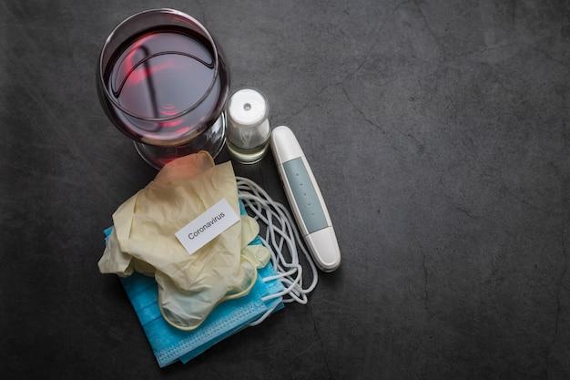 Glas rode wijn, gezichtsmasker, handschoenen en andere medische voorwerpen op donkere achtergrond