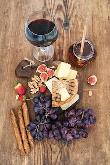 Glas rode wijn, kaasplank, druiven, vijgen, aardbeien, honing en brood sticks op rustieke houten tafel