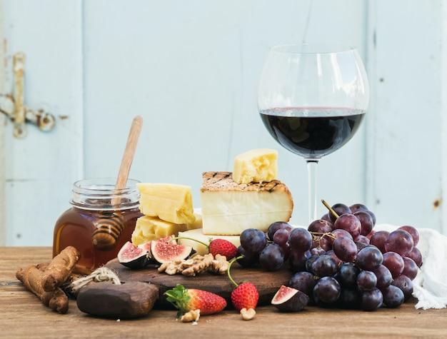 Glas rode wijn, kaasplank, druiven, vijgen, aardbeien, honing en broodstokjes op rustieke houten tafel, blauw