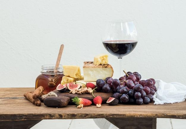 Glas rode wijn, kaasplank, druiven, vijgen, aardbeien, honing en broodstokjes op rustieke houten tafel, wit