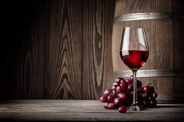 Glas rode wijn met druiven en vat
