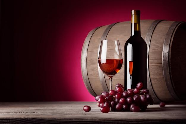Glas rode wijn met fles en druiven