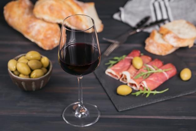 Glas rode wijn met plakjes gerookte ham of spaanse jamon serrano of italiaanse prosciutto crudo