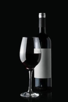 Glas rode wijn naast een fles die op zwarte muur wordt geïsoleerd