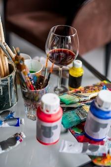 Glas rode wijn onder verfborstels en diverse verven en gouaches op de werkplek van een kunstenaar