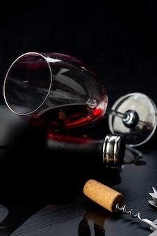 Glas rode wijn ondersteund door een fles, gemorst op de zwarte houten tafel met kurkentrekker ernaast.
