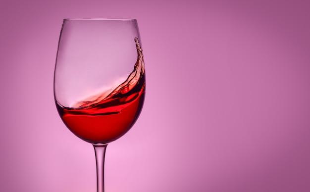 Glas rode wijn op roze geïsoleerde achtergrond. spatten en reflectie.