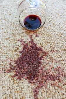 Glas rode wijn viel op tapijt, gemorste wijn op tapijt