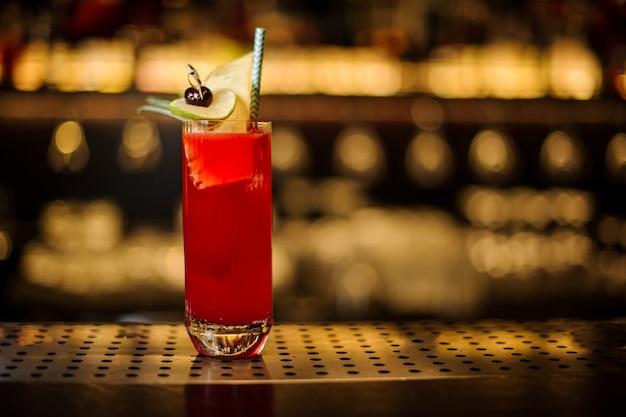 Glas rode zoete sappige drank in een cocktailglas versierd met fruit en stro