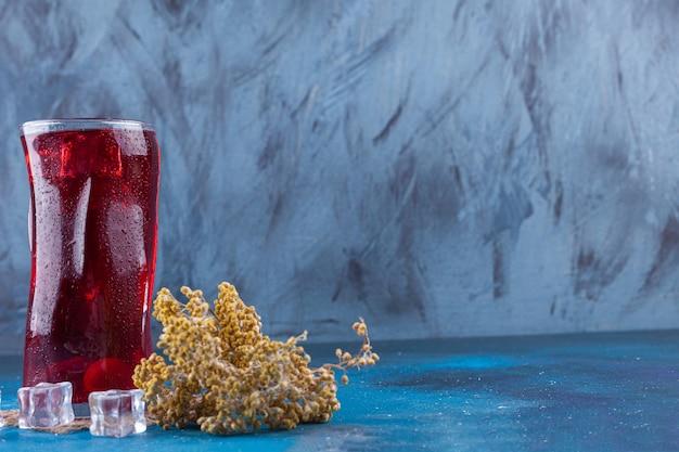 Glas rood sap met kom chocolaatjes op steenachtergrond.