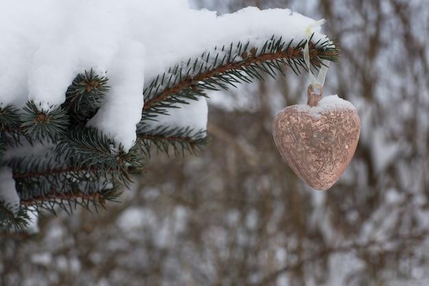 Glas roze hart opgehangen aan een vuren tak
