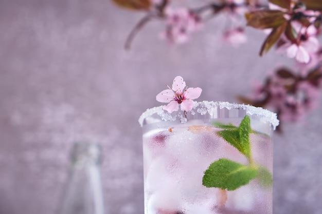 Glas roze roze champagne, cider of limonade met ijs en munt en kersenbloesems