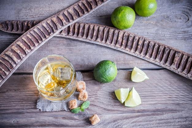 Glas rum naast limoenen bovenaanzicht