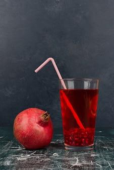 Glas sap en granaatappel op marmeren tafel