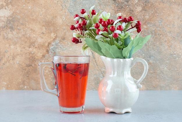Glas sap met rozenbottels en kunstbloemen op blauwe tafel.