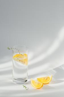 Glas schoon mineraal bruisend water met ijs en citroen op een wit oppervlak met zonneschijn