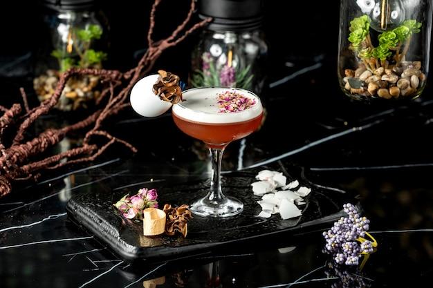 Glas schuimende cocktail gegarneerd met stukjes gedroogde rozenblaadjes en eierschaal