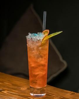 Glas sinaasappel crush cocktail gegarneerd met ijs en gedroogde sinaasappel