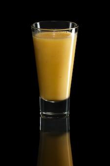 Glas sinaasappel en mangococktail op zwarte wordt geïsoleerd die