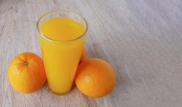 Glas sinaasappelsap en sinaasappels op houten vloer