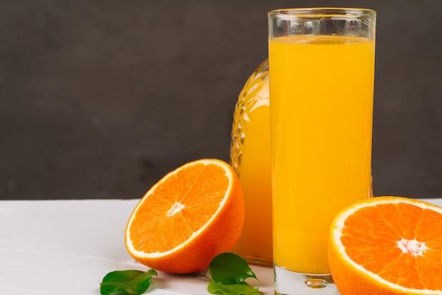 Glas sinaasappelsap en stukjes sinaasappel