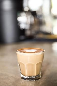 Glas smakelijke latte met liefdekunst op geweven textuur