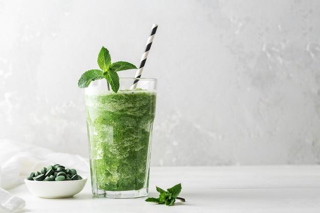 Glas smoothies met toevoeging van chlorella of spirulina met munt op een grijze betonnen achtergrond.