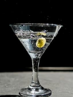 Glas spattende martini met olijf