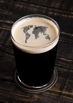 Glas stout bierbovenkant met de vorm van de aardekaart op houten achtergrond