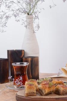 Glas thee en traditionele pistachebaklava op marmeren tafel.