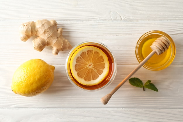 Glas thee met citroen, munt, honing, beer en gember op houten, bovenaanzicht