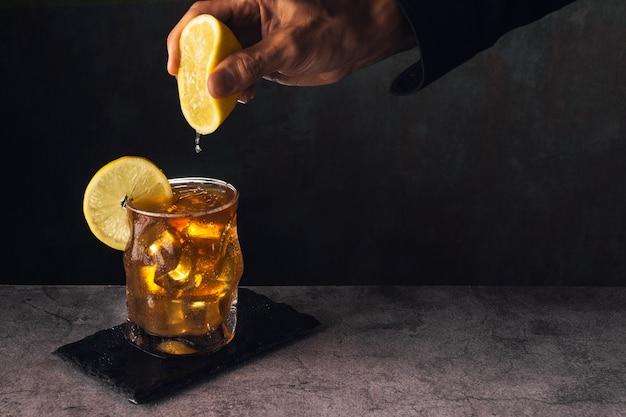 Glas thee met ijs en citroen op stenen oppervlak met donkere achtergrond en de hand van een man in een zwart shirt die het sap van een halve citroen op het glas knijpt