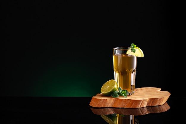 Glas thee met mojito op een houten bord.