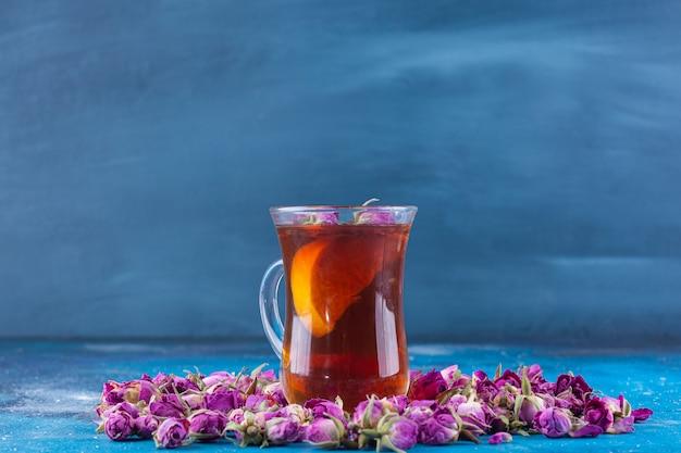Glas thee met ontluikende rozen die op blauwe lijst worden geplaatst.