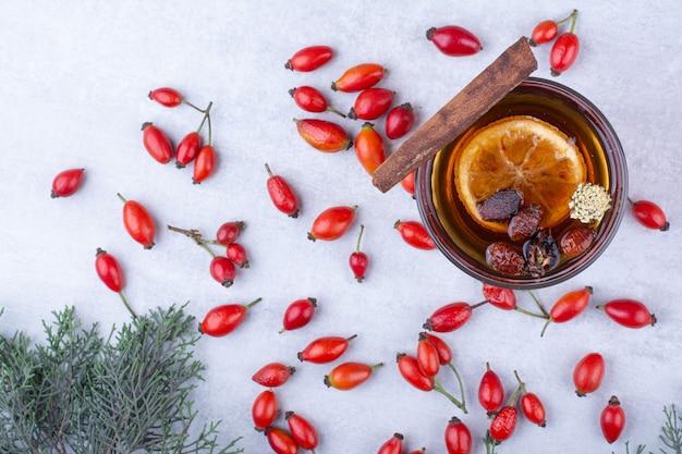 Glas thee met rozebottels, kaneelstokje en sinaasappelschijf.