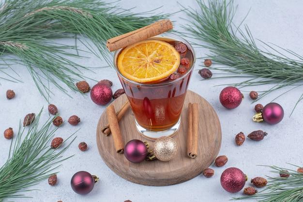 Glas thee met rozenbottels en kerstballen op het oppervlak.