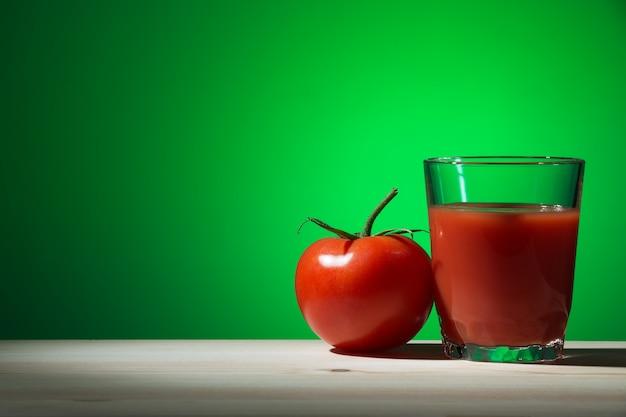 Glas tomatensap en een tomaat op een houten tafel