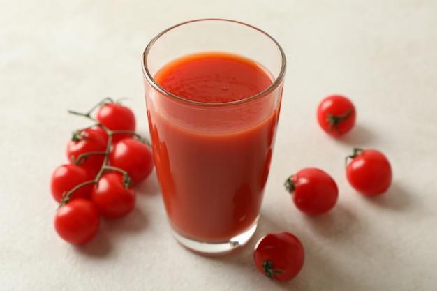 Glas tomatensap en tomaten op geweven wit