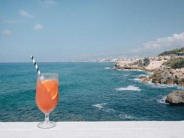 Glas traditionele italiaanse aperol spritz-cocktail in de buurt van de oceaan