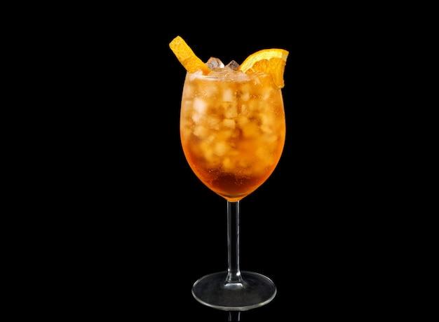 Glas van aperol spritz cocktail op een zwarte achtergrond wordt geïsoleerd die