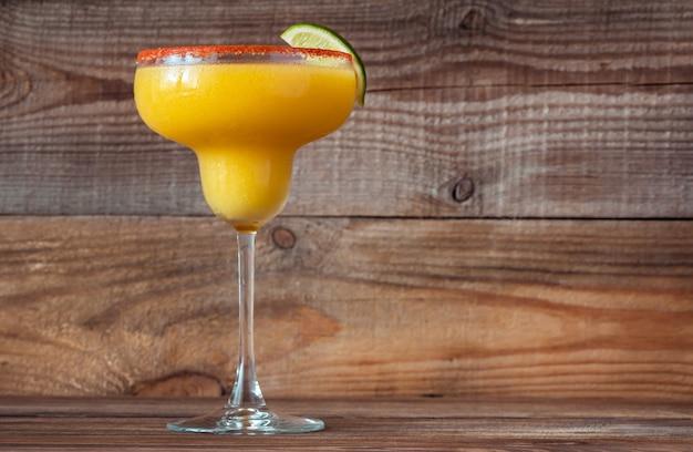 Glas van frozen mango margarita cocktail gegarneerd met paprika zoute rand