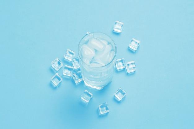 Glas verfrissend koud water met ijs en ijsblokjes op een blauwe oppervlakte.
