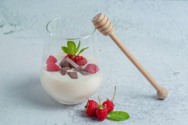 Glas verfrissende frambozenmilkshake voor ontbijt op grijze ondergrond.