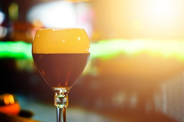 Glas vers donker bier op rustieke barachtergrond.