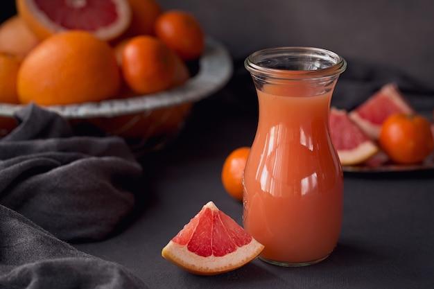 Glas vers geperst grapefruitsap met verse citrusvruchten op donkere achtergrond. grapefruits, sinaasappels en mandarijnen