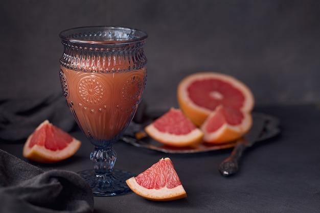 Glas vers geperst grapefruitsap met verse citrusvruchten op donkere achtergrond. ruimte voor tekst.