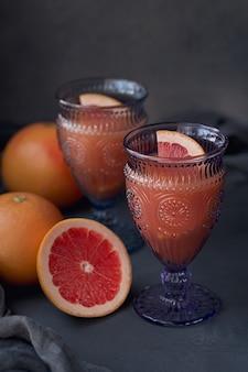 Glas vers geperst grapefruitsap met verse citrusvruchten op donkere achtergrond.